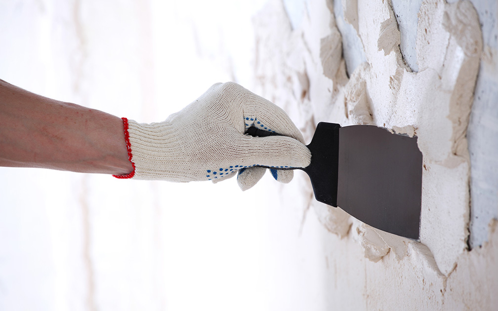 Hand with work glove and pallet knife creating a stucco texture wall